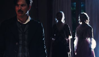Christian Gray as Edgar Allan Poe in foreground, two shadowy figures of women in the background