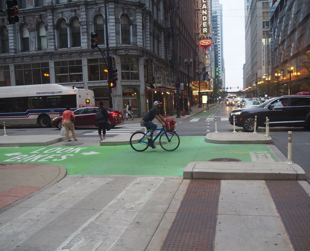 Bicyclist riding through a downtown Chicago intersection