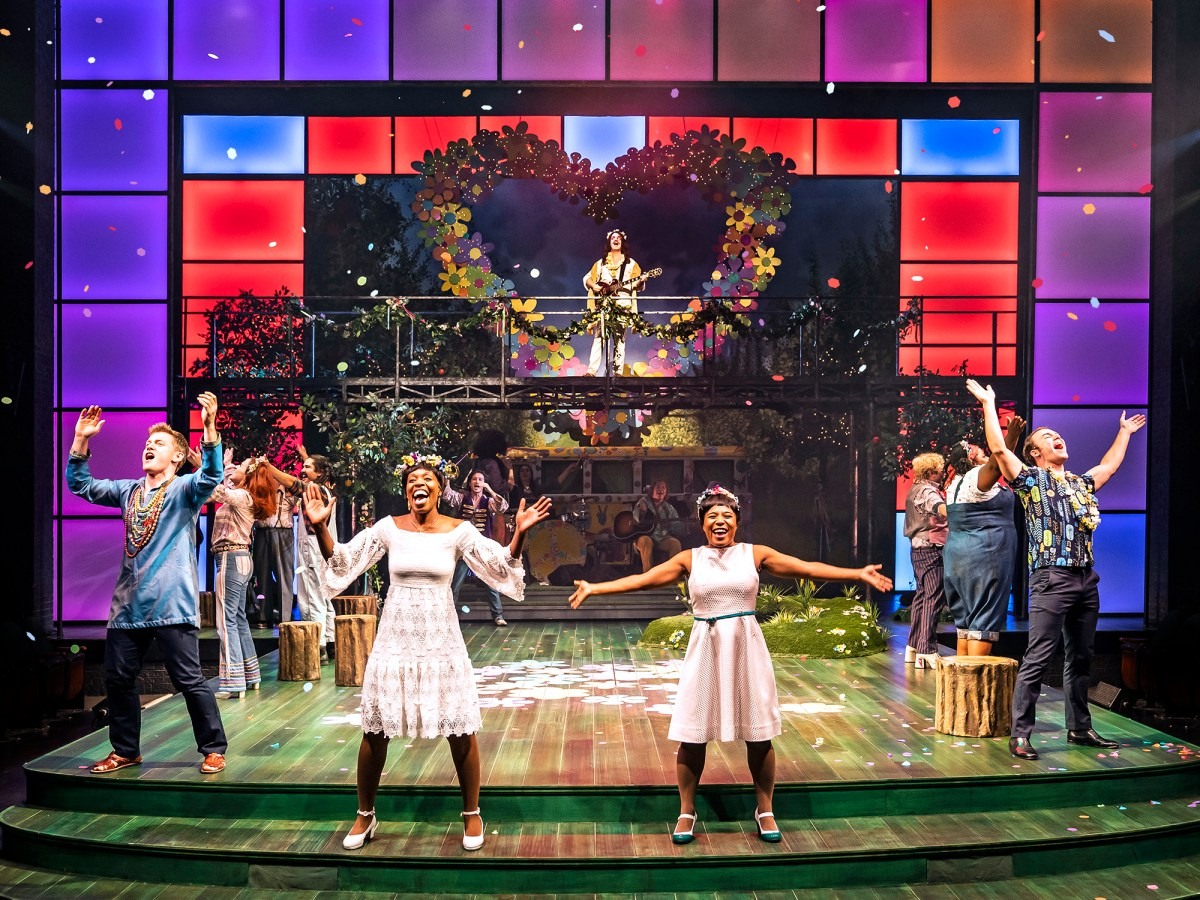 The company of As You Like It at Chicago Shakespeare dressed like flower children of the 1960s