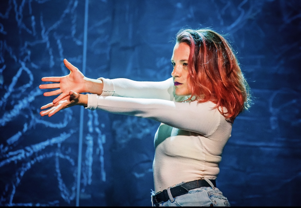 Erin Kilmurray, wearing a white shirt and jeans, stands with arms outstretched to the left of the page in front of a blue backdrop.