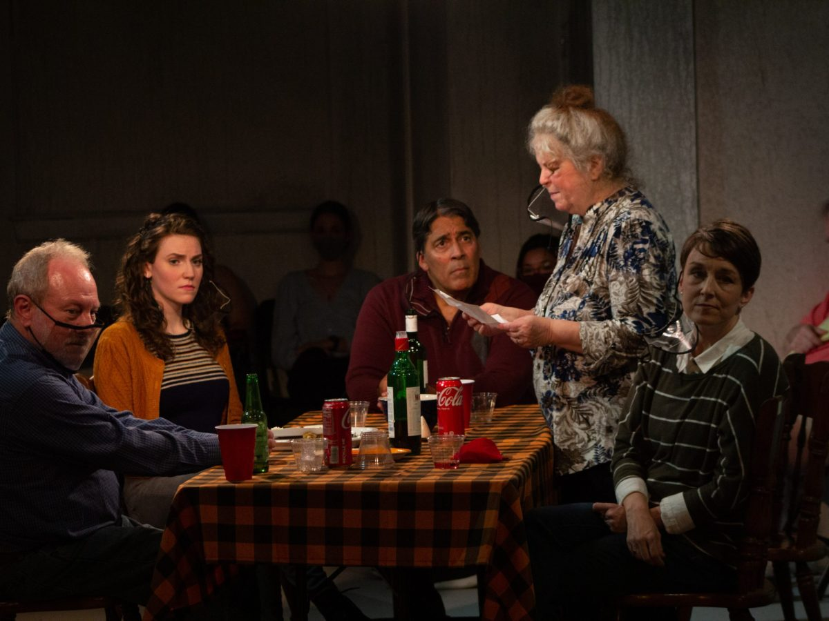 A family sits at a table as an older woman reads a prayer