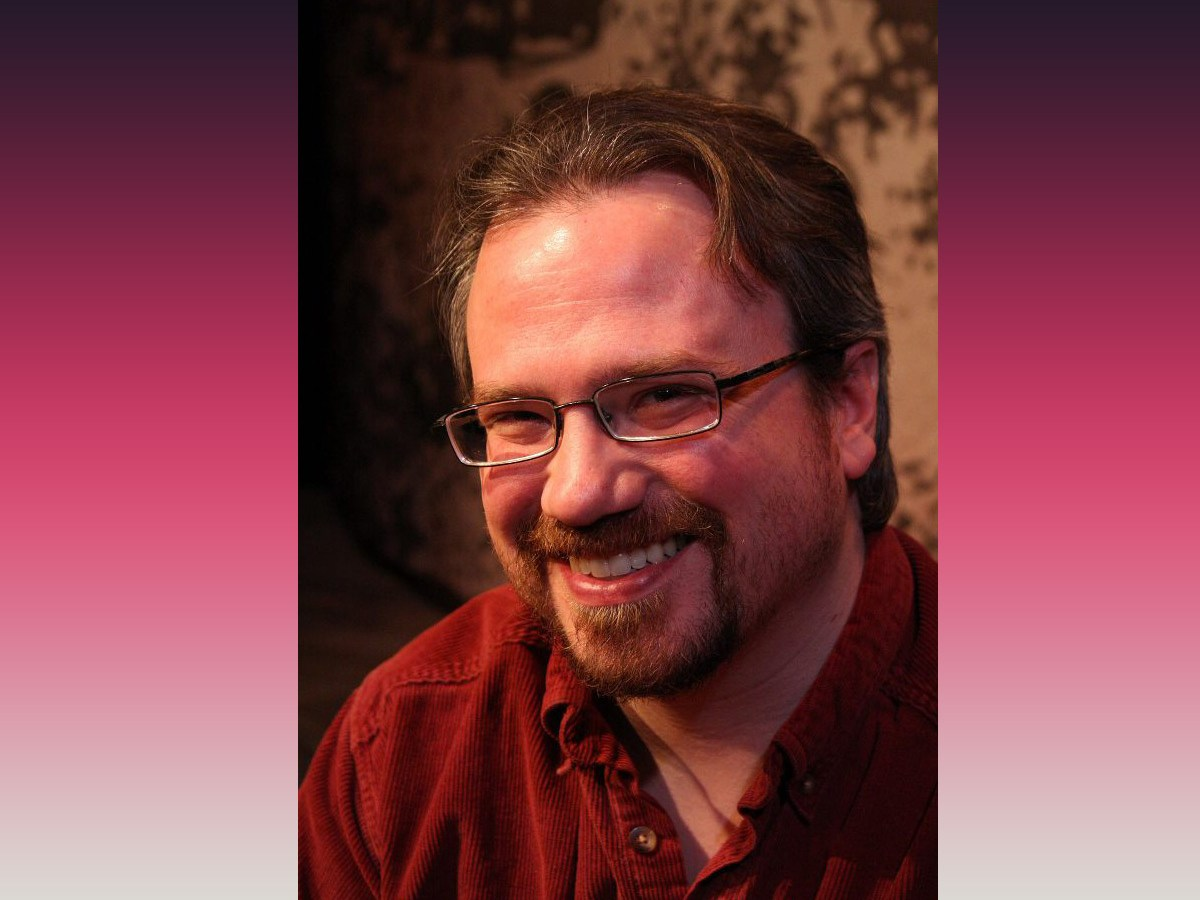 Photo of playwright Joseph Zettelmaier on pink background, wearing red shirt with glasses