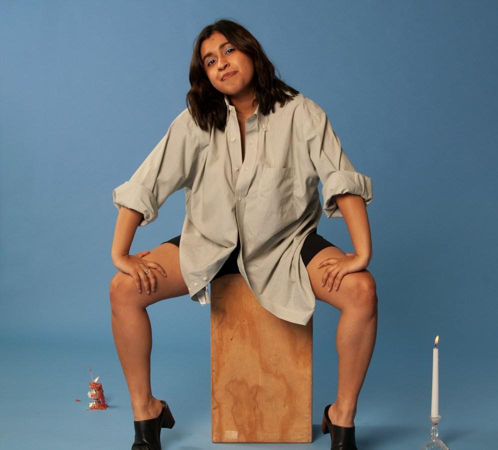 Mia Joy sitting on a wood block against a blue backdrop