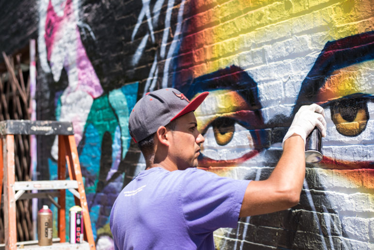 Milton Coronado paints a wall on 51st Street in the Back of The Yards neighborhood. The graffiti wall is a collaboration with other artists.