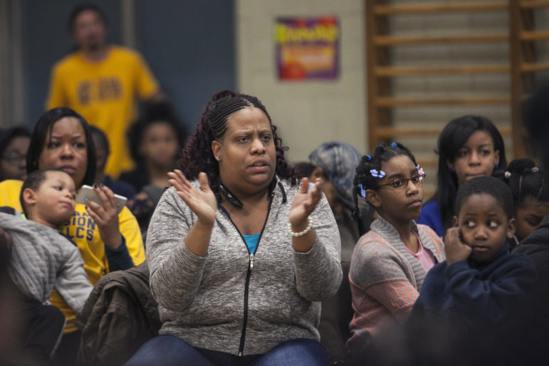 Florence Percy applauds after Illinois State Charter School Commission members question Chicago Public Schools' representatives during a public hearing on Feb. 16 about the closure of Bronzeville Lighthouse Charter School.