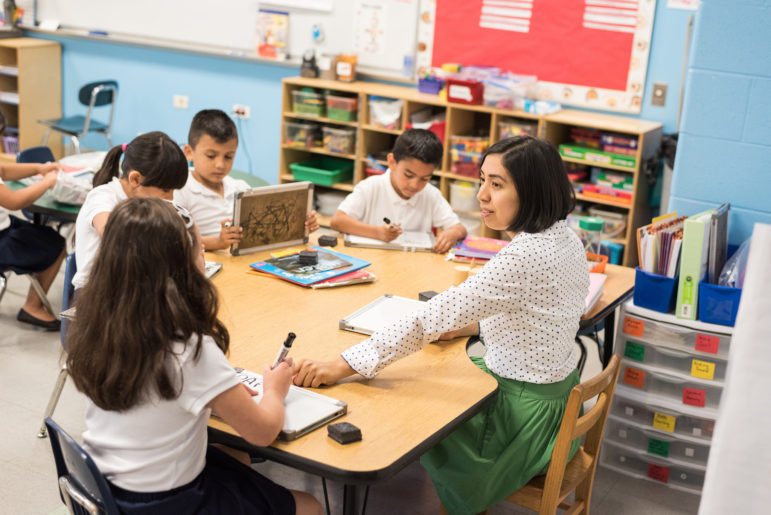 Kindergarten bilingual teacher Yesenia Hinojosa works with a small group on pronunciation and spelling in Spanish at Hurley Elementary.