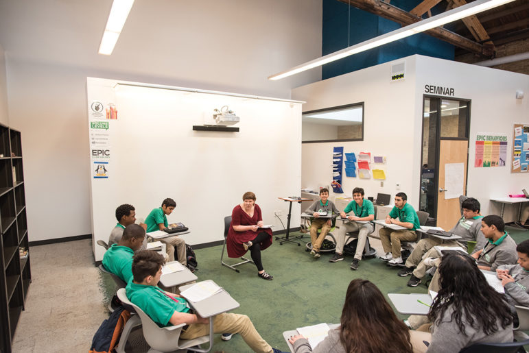 """Ashley Haywood, a ninth-grade English teacher at Intrinsic Schools' Belmont campus, leads a """"Socratic Seminar"""" with a small group while her two co-teachers work with other students in a large, open pod. Behind her is a projector mounted to a wall covered in whiteboard paint — which Intrinsic officials say is a cheap alternative to interactive whiteboards."""