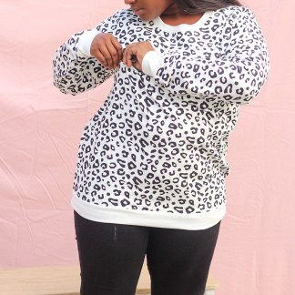 Mother wearing a breastfeeding jumper which is black and white leopard print, she is holding the zipper which allows for access to the breasts