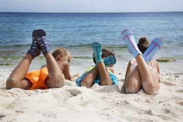Kids hanging out on beach with Duukies Beachsocks on