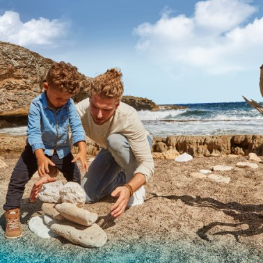 Father and son playing with on the background one of the many beautiful landscapes of Curacao