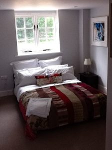View of Bedroom 1 with double bed and pretty, white-painted casement windows above the head of the bed
