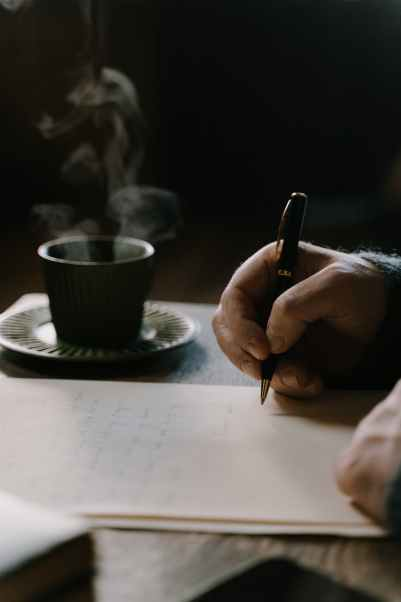 person writing a letter on table