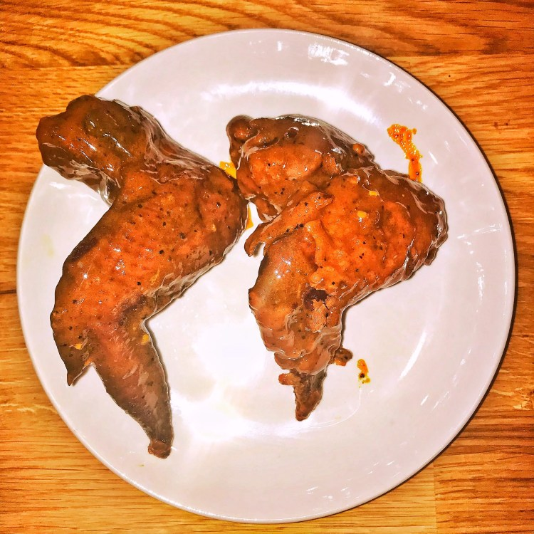 Two whole, fried chicken wings smothered in Memphis Honey Hot Sauce