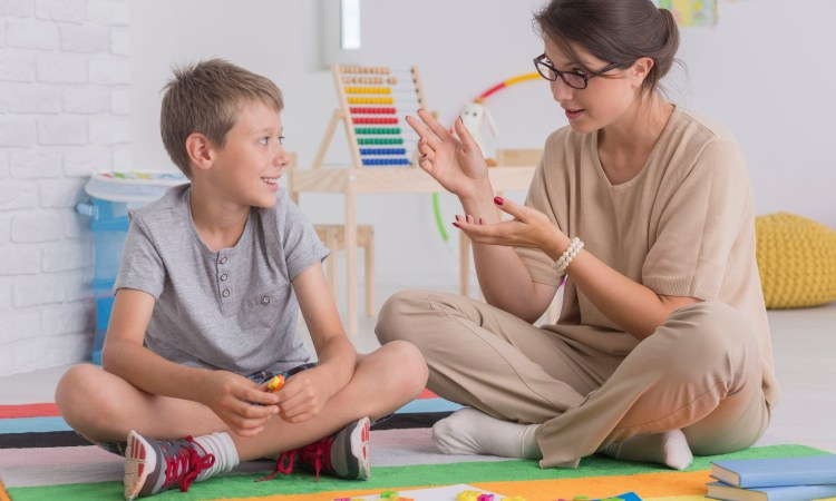 Therapist sitting on floor with child client