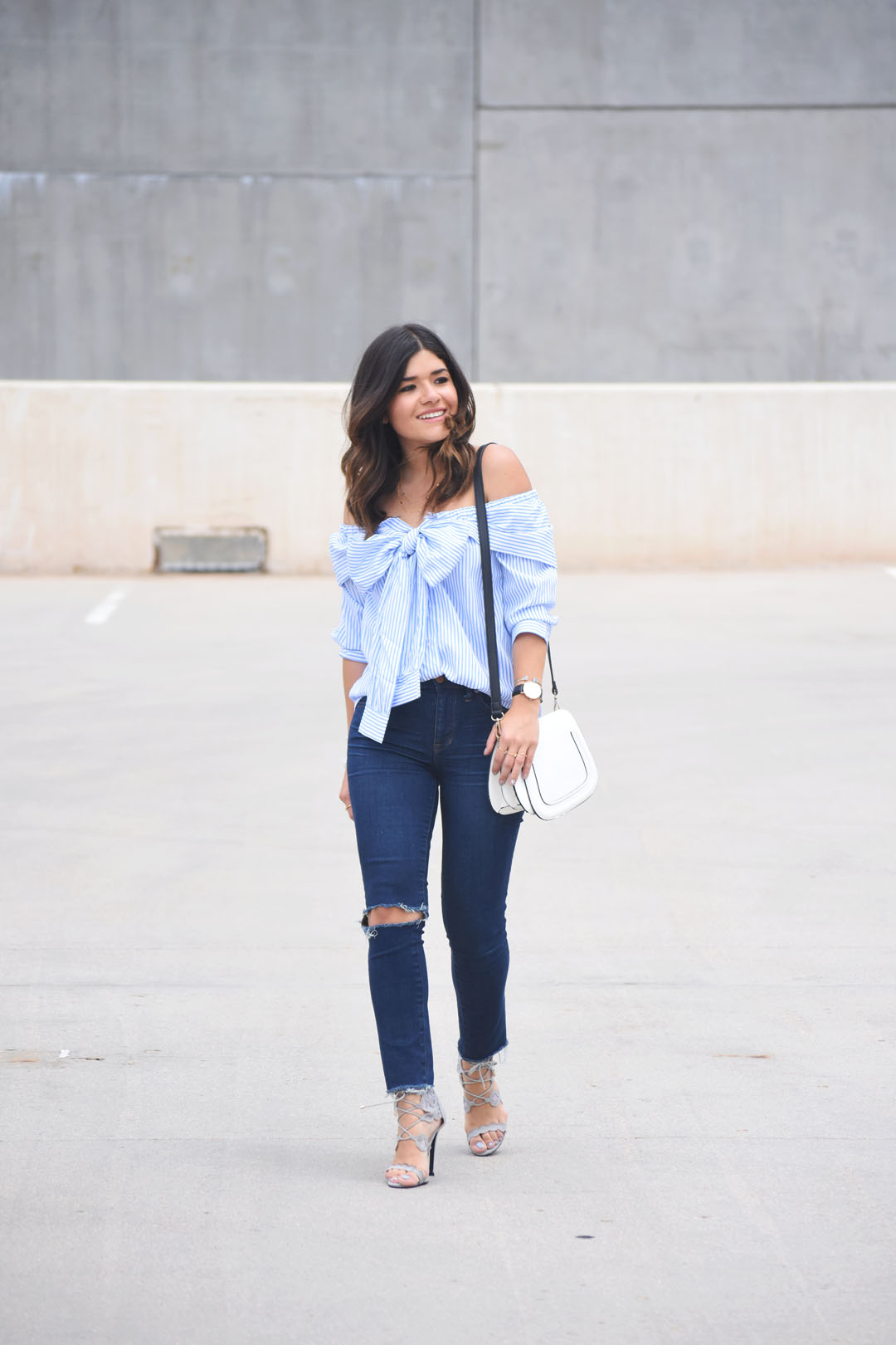 Carolina Hellal of Chic Talk wearing a tie front off the shoulder top via SheIn, Madewell jeans, and grey lace up sandals via Public Desire.