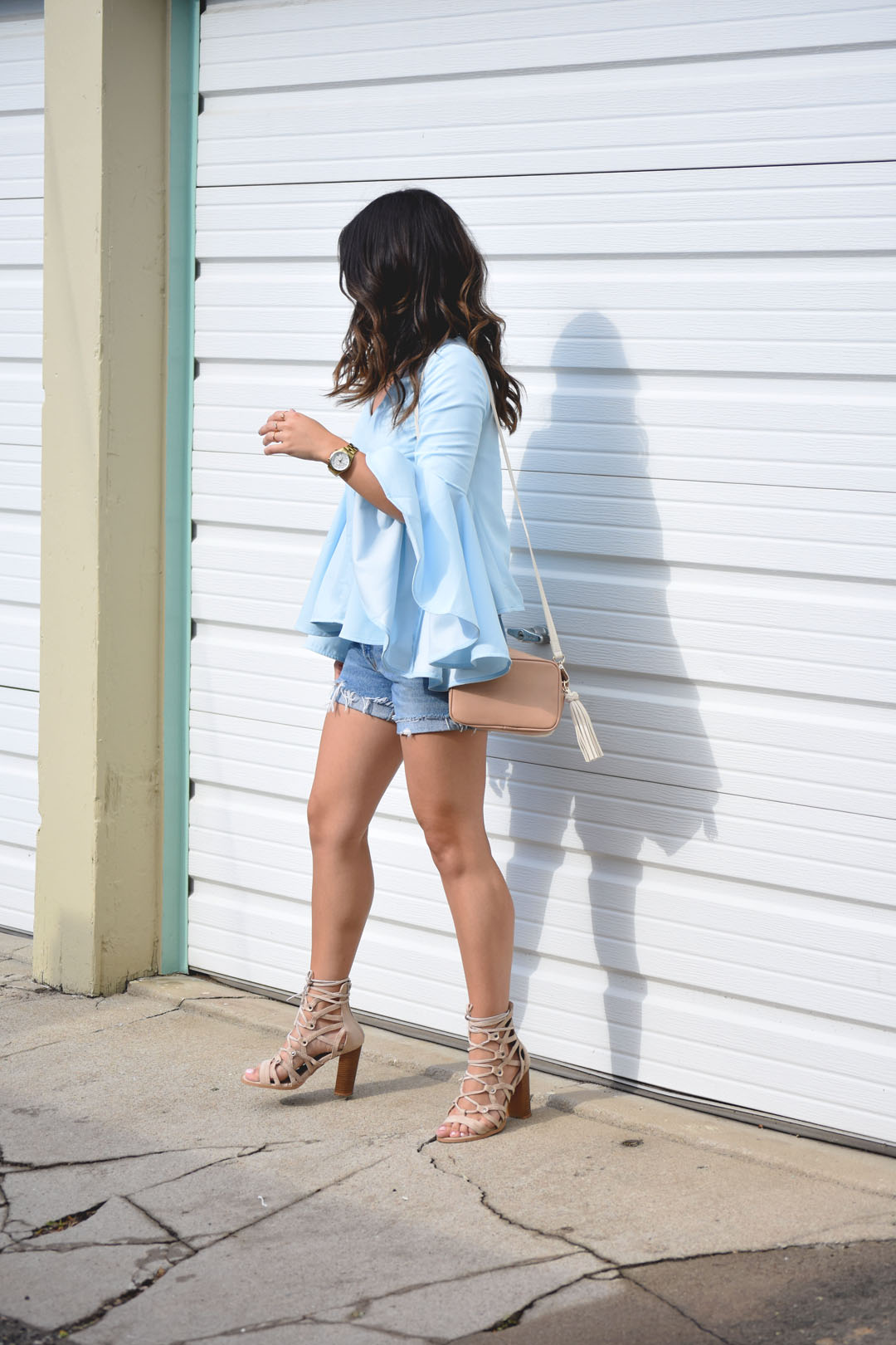 Carolina Hellal of Chic Talk wearing the serene blue top with bell sleeves by Chicwish, vintage denim shorts and Lasula Boutique lace up sandals.