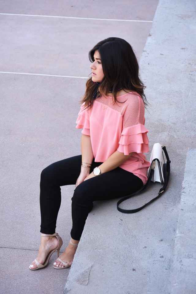 Carolina Hellal of Chic Talk wearing a VIPme pink top, Christian Paul watch, sole society bag, and Citizen of humanity black skinny jeans