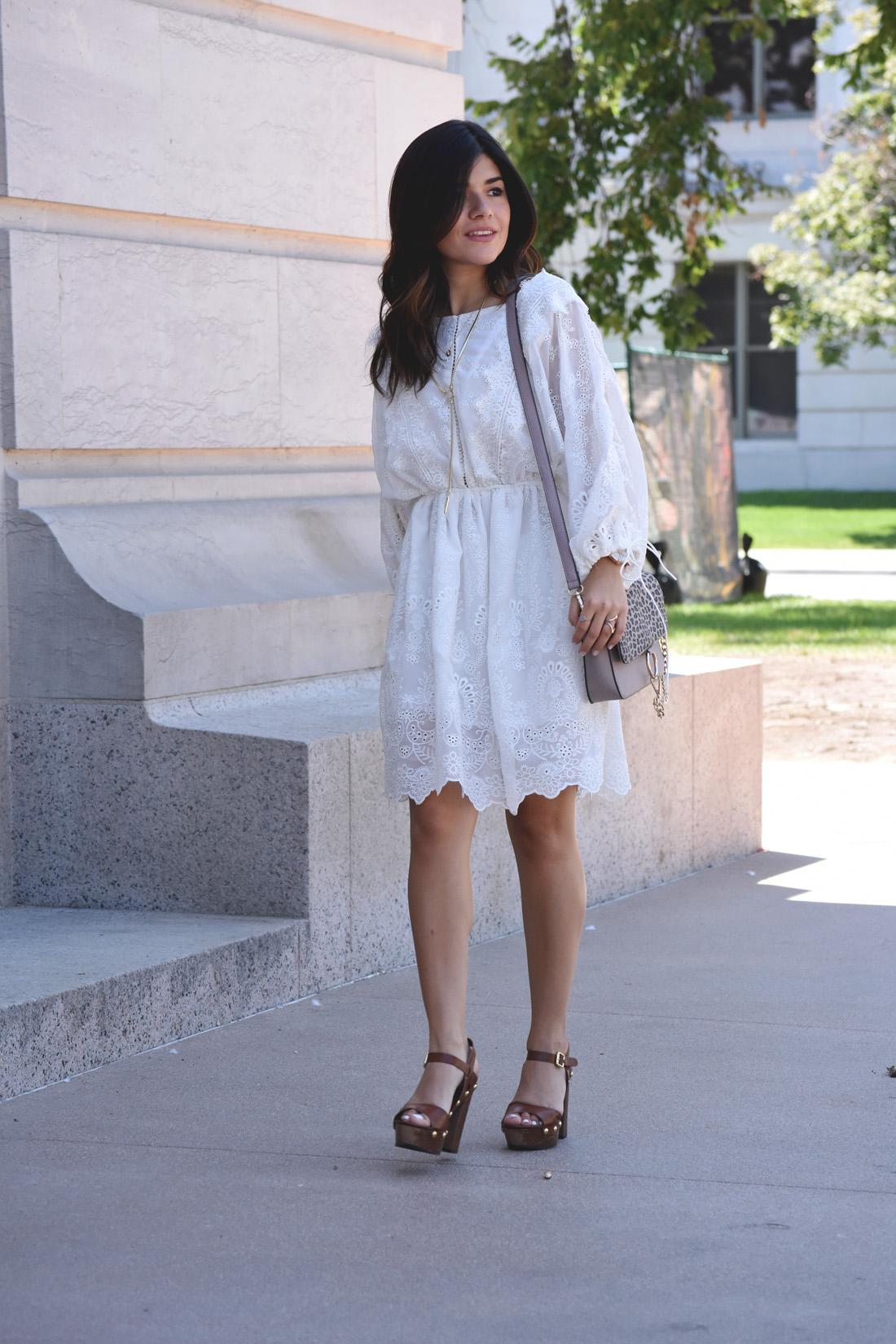 Carolina Hellal of Chic Talk wearing a VIPME white dress, wooden platform sandals, and Kendra scott gold accessories.