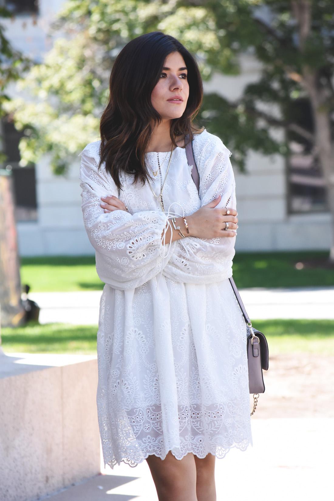 Carolina Hellal of Chic Talk wearing a cutout white summer dress via VIP ME, , Kendra Scott gold bracelets, and necklace.