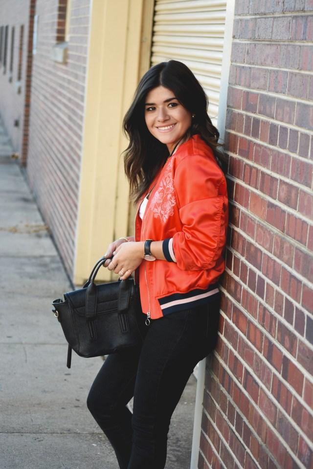 Carolina Hellal of Chic Talk wearing a red H&M bomber jacket and black Mellow handbag world crossbody bag
