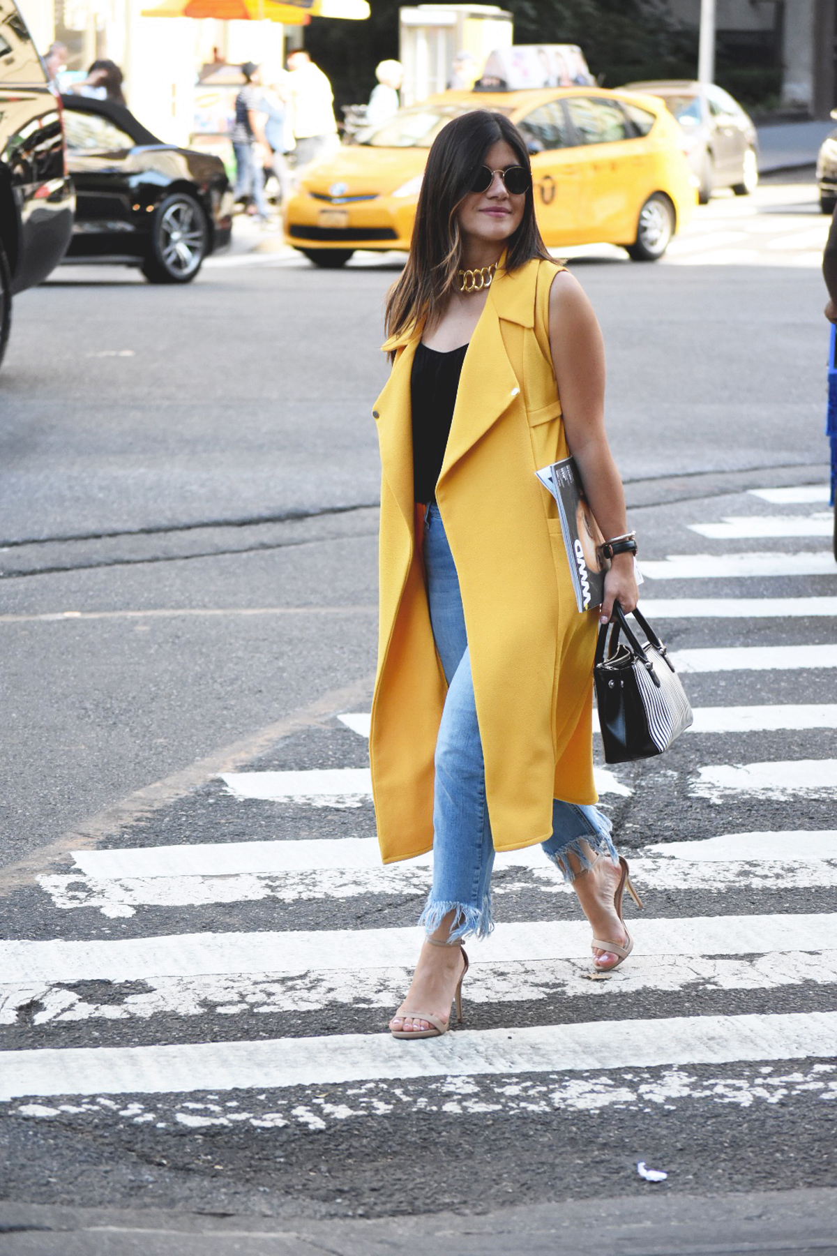 Carolina Hellal of Chic Talk wearing a Shein yellow maxi vest, Top shop fringed hem jeans, Rayban rounded sunglasses, Ralph Lauren striped bag, and Steve Madden beige strap sandals