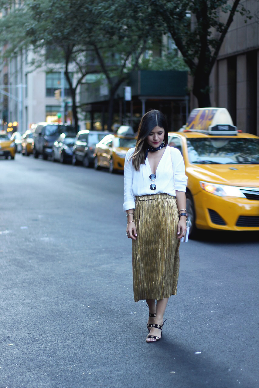Carolina Hellal of Chic Talk during NYFW wearing a SheIn gold pelated skirt, white oversized draped top, and Public Desire black sandals