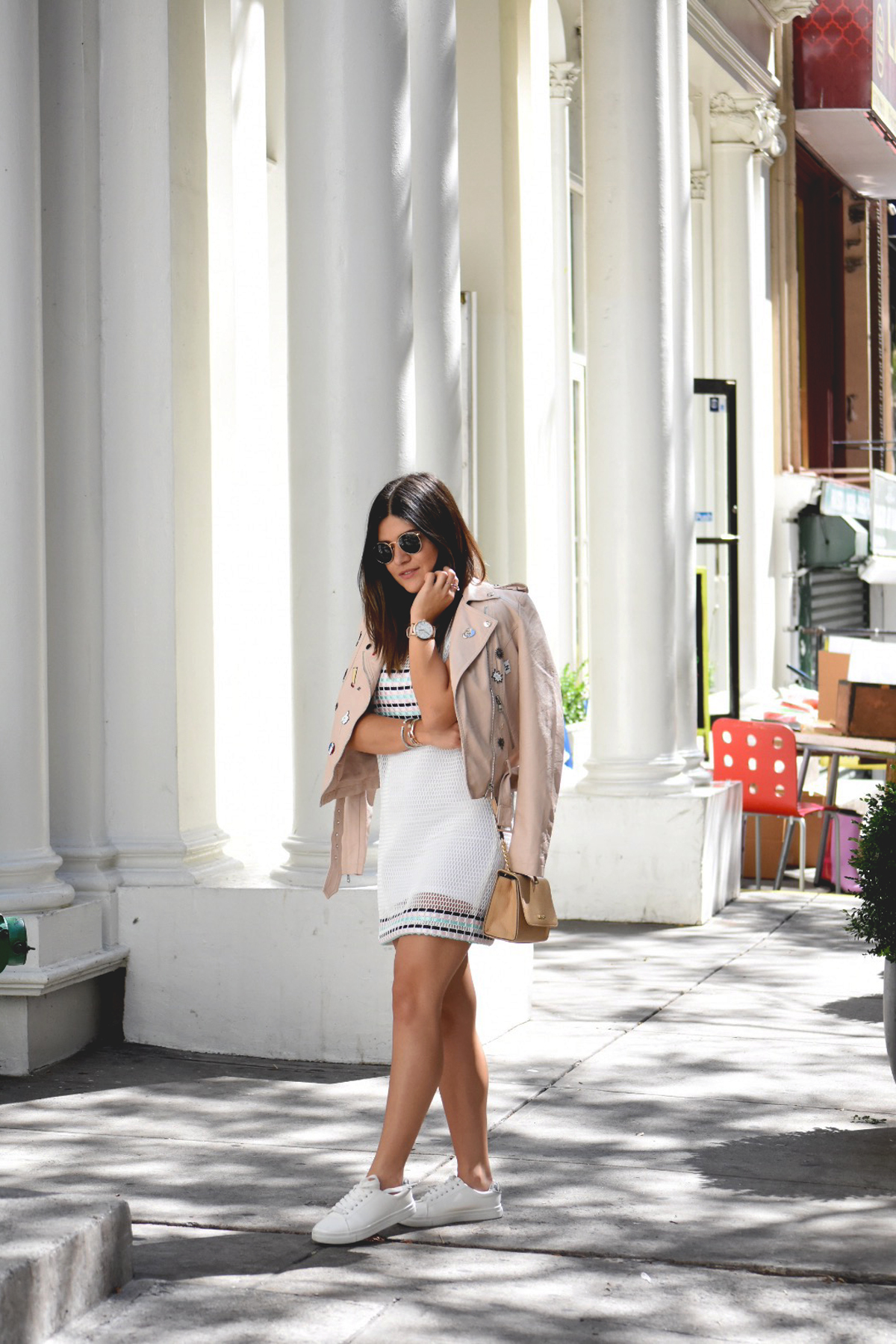 Carolina Hellal of Chic Talk during NYFW wearing a Dezzal faux leather jacket, tobi mesh dress, and h&m white sneakers