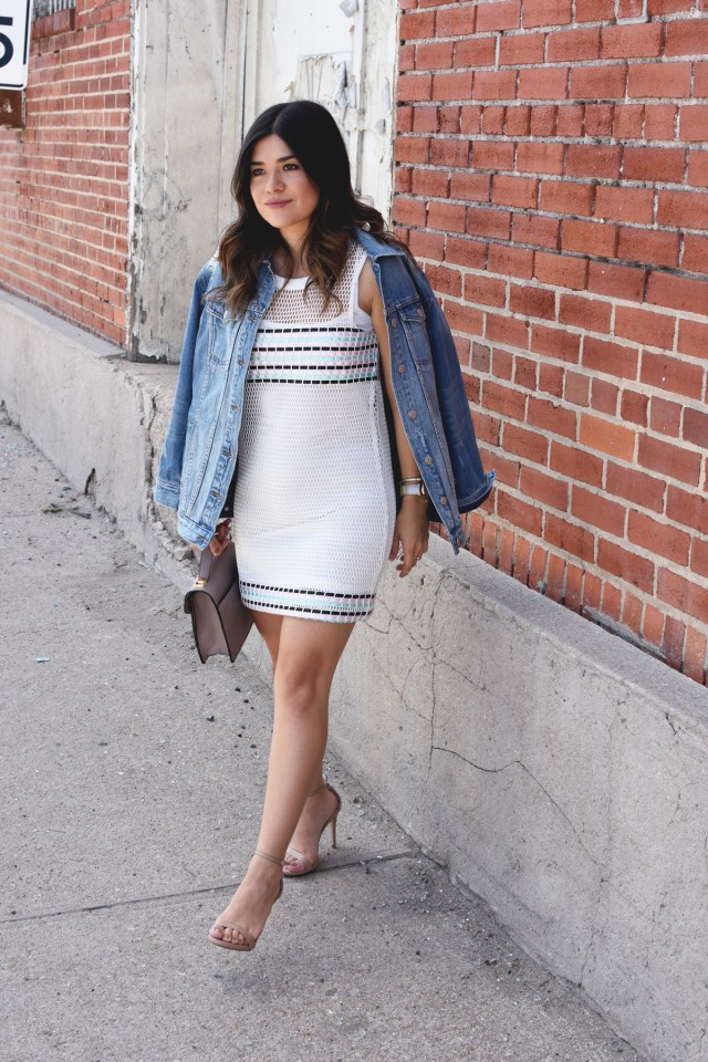 Carolina Hellal of chic Talk wearing a Madewell Oversized denim jacket, Tobi mesh dress, Steve Madden nude strap sandals, and Timex gold watch