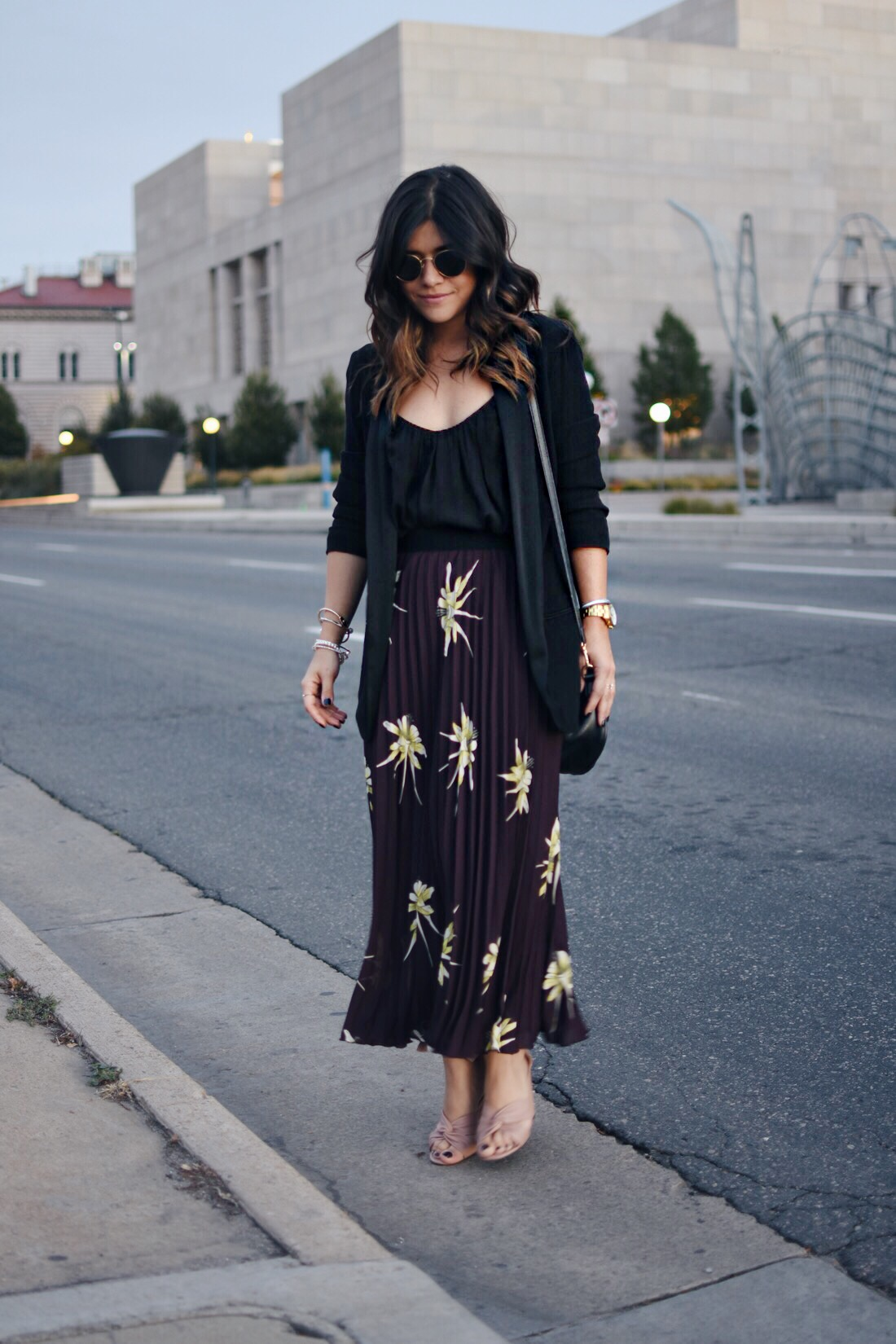 Carolina Hellal of Chic Talk wearing an H&M pleated print skirt, black blazer, and Topshop blush sandals.