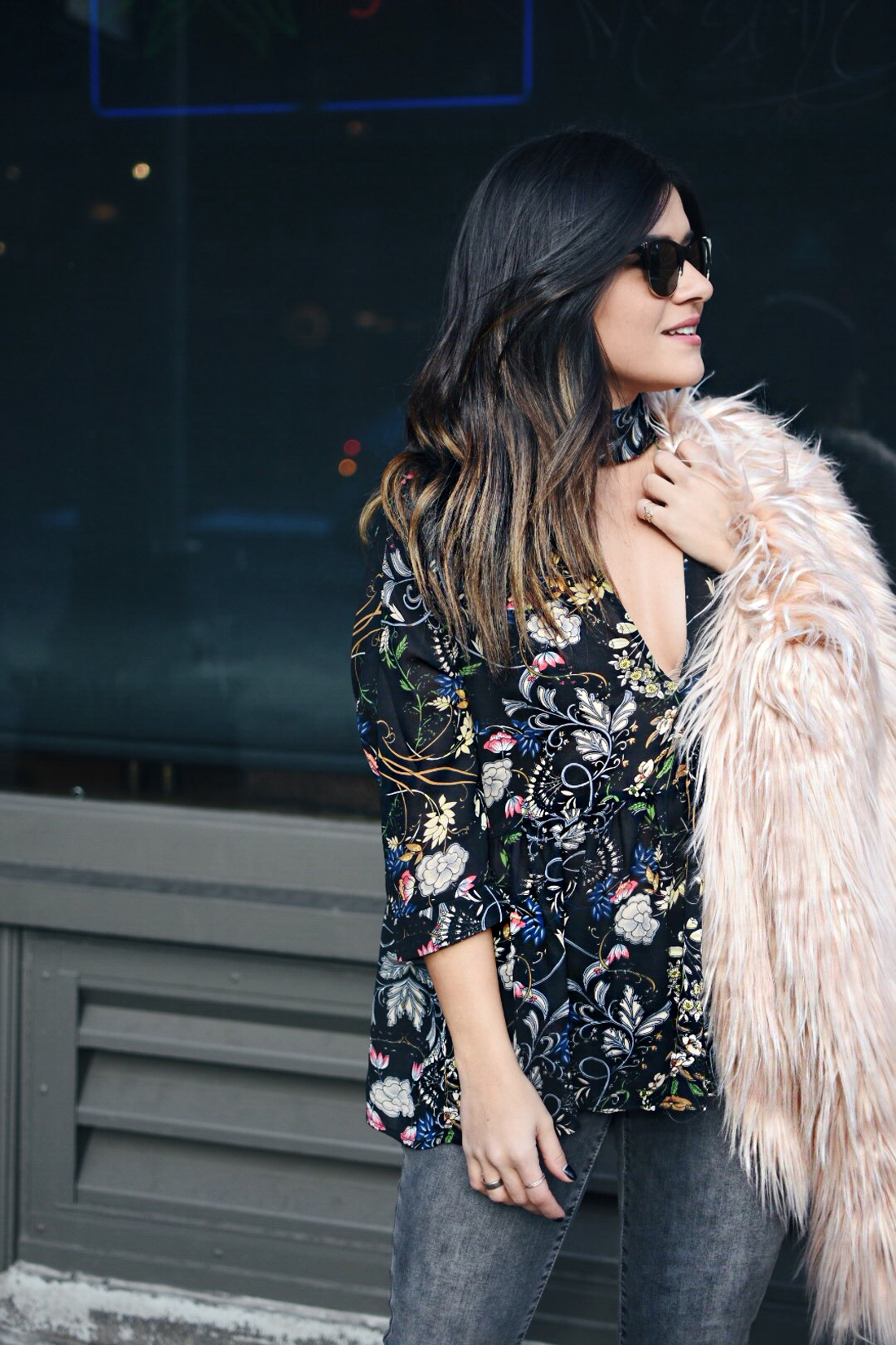 Carolina Hellal of Chic Talk wearing a floral top, furry pink coat, Madewell jeans, and h&m black booties