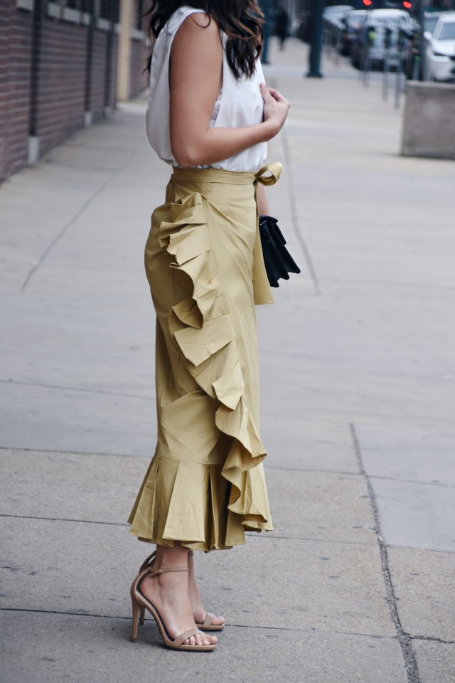 Carolina Hellal wearing a ruffled style mafia skirt, tobi white v-neck top, boyfriend denim jacket, Steve Madden strap sandals, and Rebecca Minkoff