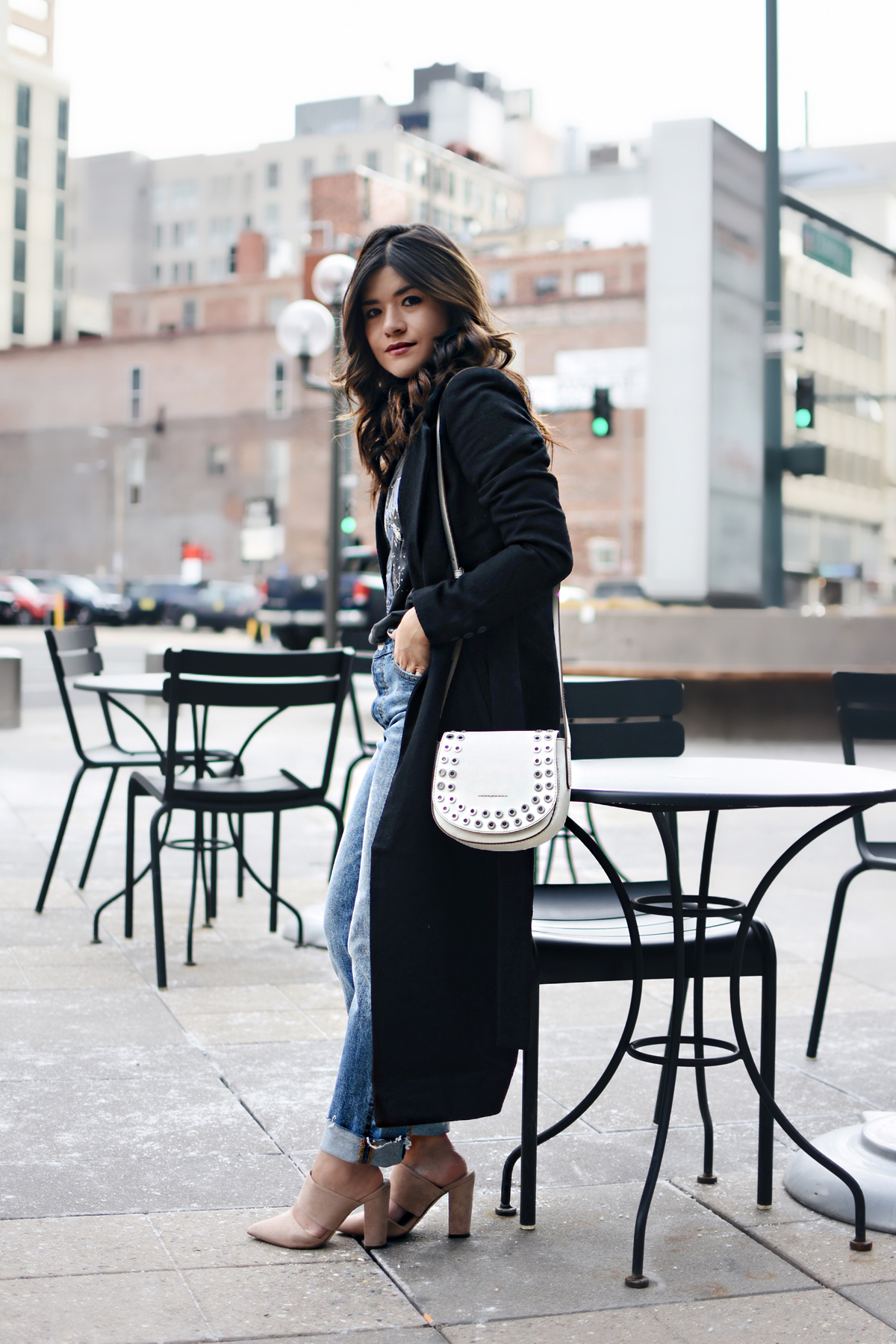 Carolina Hellal of Chic Talk wearing an H&M graphic t-shirt, H&m girlfriend jeans, Frey company white crossbody bag, and NA-KD fashion mules and black coat.