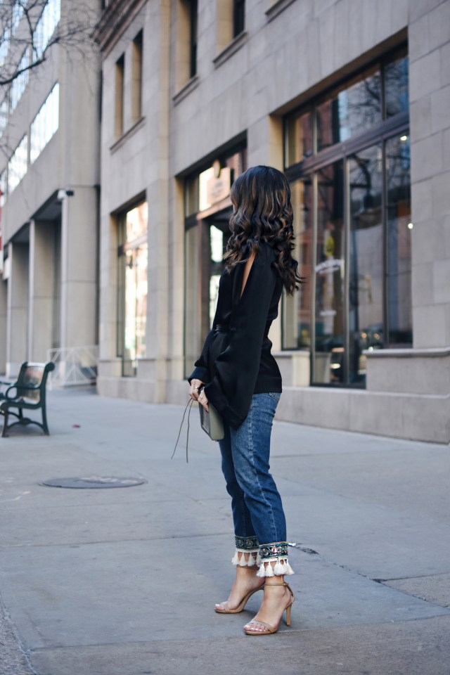 Carolina Hellal of Chic Talk wearing Topshop straight jeans with tassles, NA-KD black cold shoulder top, Rebecca Minkoff bag and Steve Madden nude strap sandals