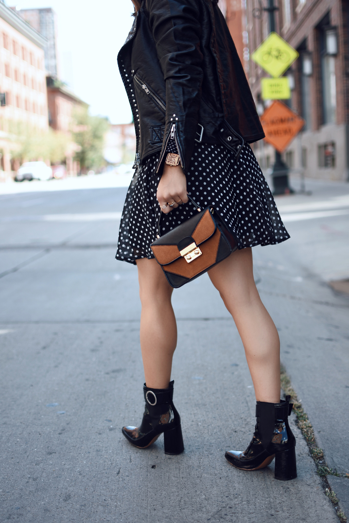 Carolina Hellal of Chic Talk wearing a Free People faux leather jacket, Renamed polka dot dress and h&m black patent leather booties.