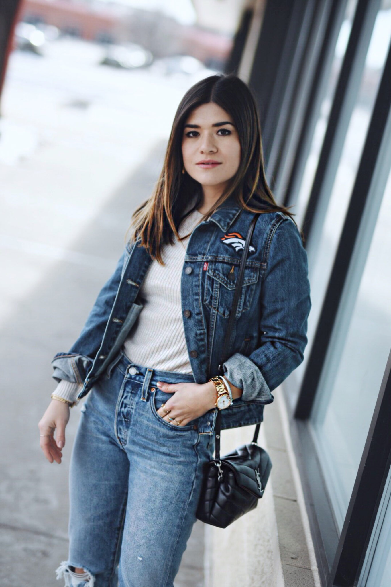 Carolina Hellal of Chic Talk wearing a Levi's Denver Broncos Jacket, Levi's 501 jeans, YSL crossbody bag and Public Desire boots
