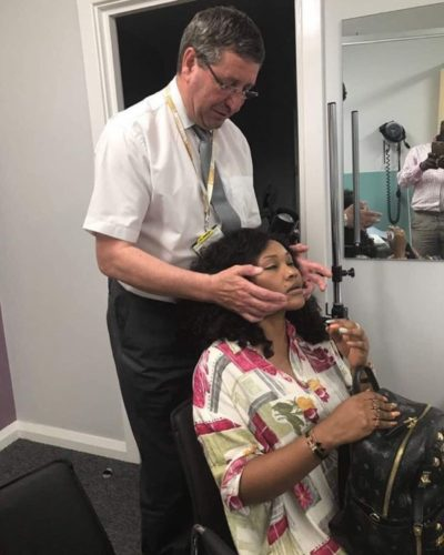 Aigbe's face being massaged by a face surgeon in London
