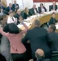 Wendi Murdoch in pink fighting off the shaving cream pie heading for Murdoch's face.
