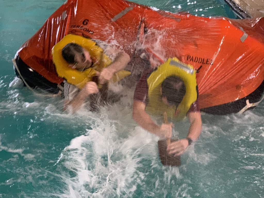 RYA MCA Sea Survival Students paddling a life raft in simulated spray