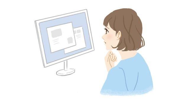 「パソコンを見て電報を考える女性」のイメージ画像