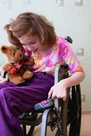Girl in Wheelchair holding a Stuffed Bear
