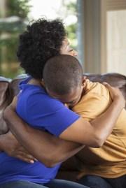 Black/African-American mother hugging her teenage son, his head on her shoulder.