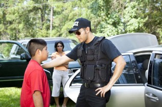 A Latino policeman questions an elementary aged Latino boy, his hand on his shoulder, while the Mom watches in the background.