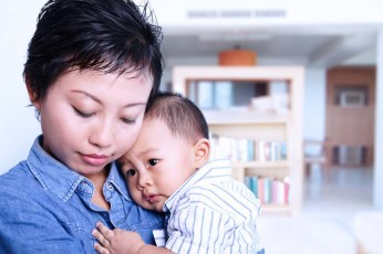 An Asian woman holding a baby in front of a blurry bookcase