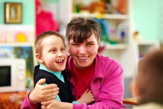 woman holding a boy that is smiling with a blurry background