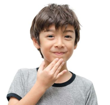 "A young Latino boy smiles and signs ""thank you"" in American Sign Language."