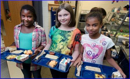 children holding school lunch trays