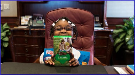 little girl poses with box of Girl Scout cookies