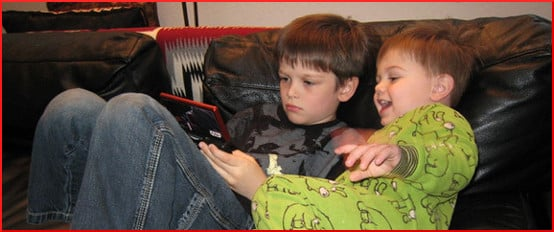 [two brothers looking at a tablet computer]