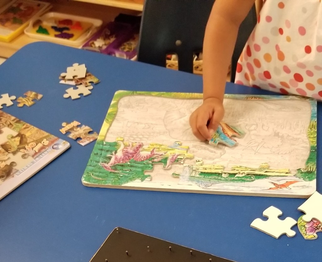 Child doing a puzzle at dinosaur summer camp