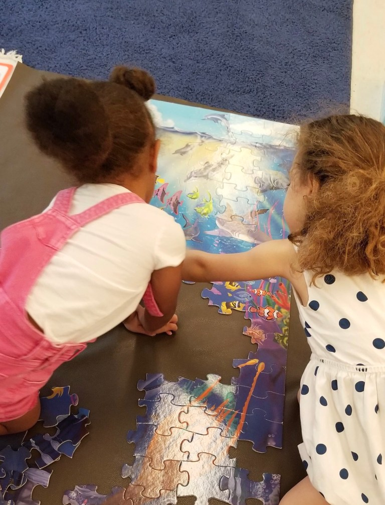 Two children building a puzzle demonstrates character development in early childhood classrooms.